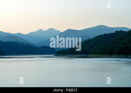 Serene lake at sunset. Lake Vidraru is an artificial lake in Fagaras mountains, Arges county, Romania - Stock Photo