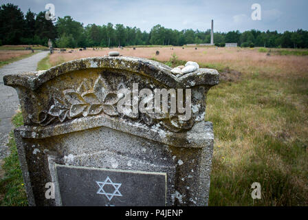 The weathered and bearing the Star of David at graves in the memorial grounds of Bergen-Belsen concentration camp. - Stock Photo