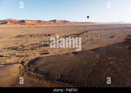 Colorful hot-air balloon flying over the high mountains in Namibia. High altitude. ( Namibia, South Africa) - Stock Photo