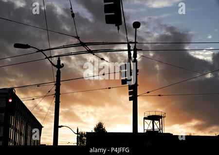 High-voltage electricity wires and traffic lights silhouetted against sunset. - Stock Photo