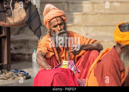 Hindu sadhu holy man, sits on the ghat, seeks alms on the street in Jaisalmer, Rajasthan, India . Close up - Stock Photo