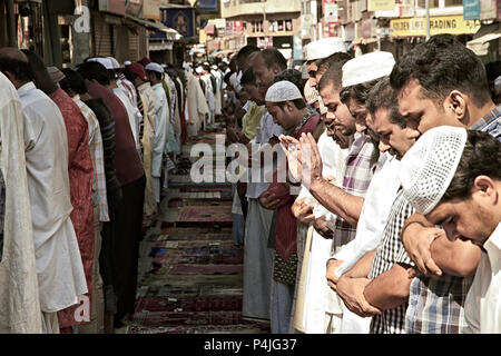 Muslim Praying Together outside on a street in Dubai - Stock Photo