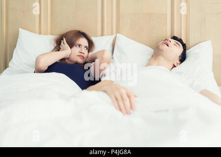 Annoyed Asian wife blocking her ears from noise of husband snoring in bedroom at home. Young couple have problem with man's snoring. - Stock Photo