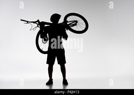 silhouette of trial biker holding bicycle on shoulders on white - Stock Photo