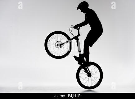 silhouette of trial biker performing bunny hop on white - Stock Photo