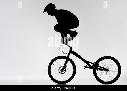 silhouette of trial biker standing on handlebars with hands on white - Stock Photo