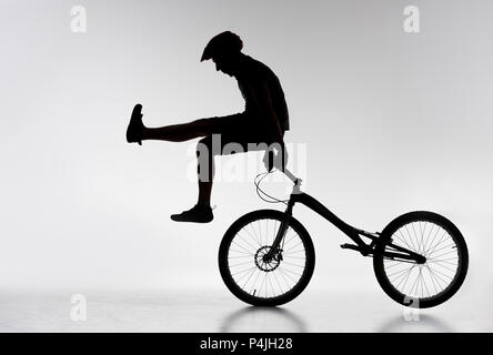 silhouette of trial cyclist standing on handlebars with hands on white - Stock Photo