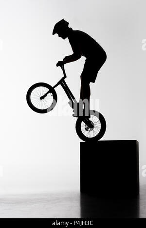 silhouette of trial biker performing stunt while balancing on cube on white - Stock Photo