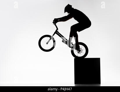 silhouette of trial cyclist performing back wheel stand while balancing on cube on white - Stock Photo