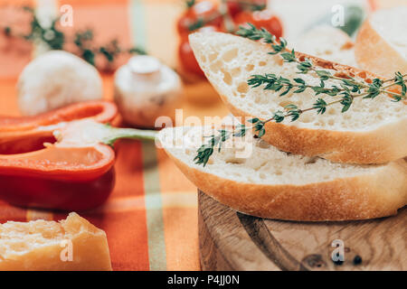 close-up view of fresh sliced baguette on wooden cutting board and parmesan cheese with bell pepper and mushrooms on table - Stock Photo