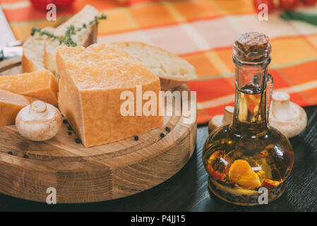 baguette and parmesan cheese on wooden cutting board and oil with spices in glass jug on table - Stock Photo