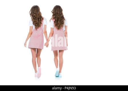 rear view of young twins holding hands isolated on white - Stock Photo
