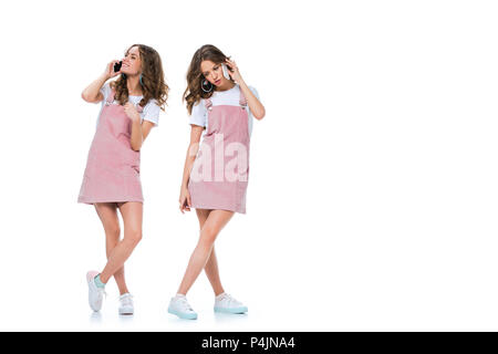 happy and angry twins talking by smartphones isolated on white - Stock Photo