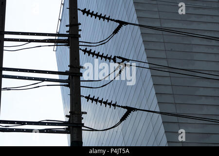 looking up at cables, transformers and architecture in Bangkok - Stock Photo