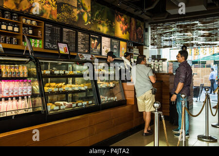 Middle age men conversing at Starbucks counter, Gurugram, India - Stock Photo