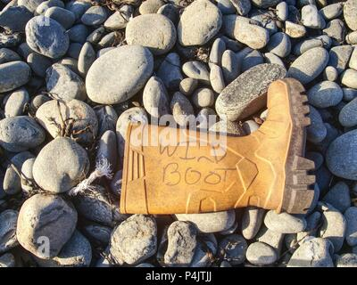 Plastic and rubbery rubbish washed up on a stony beach.  Photo showing pollution problem. Dangerous garbage ejected from the sea on remote beaches. - Stock Photo
