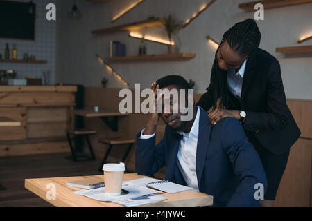 stressed african american businessman with colleague doing massage on meeting in cafe - Stock Photo