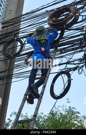 Worker on ladder working on overhead cables and wires - Stock Photo