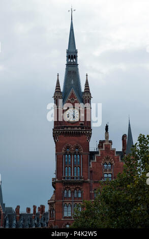 Spired clock tower at St. Pancras International Train Station, St. Pancras Kings Cross, London. Trees in foreground, portrait, copy space. - Stock Photo