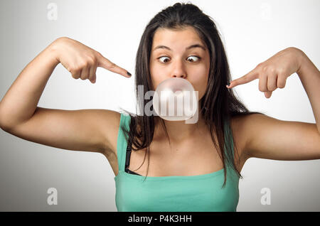 Pretty young girl with crossed eyes blowing a big chewing gum bubble - Stock Photo