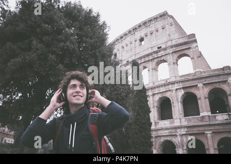 Vintage looking image of handsome young man with headphones listening to music in front of Colosseum in Rome - Stock Photo
