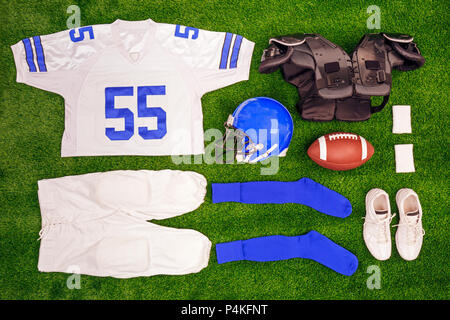 A flat lay arrangement of an Americam Football kit with ball, shirt, helmet and protective pads. - Stock Photo