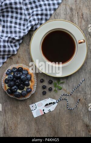 A cup of coffee and a blueberry tartlet - Stock Photo