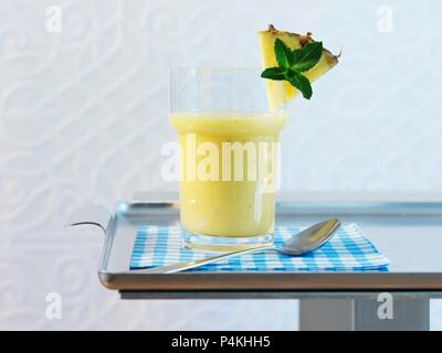 A glass of pineapple and banana smoothie - Stock Photo