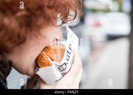 A red-haired teenager biting into a hamburger - Stock Photo