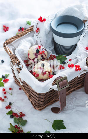 Vegan redcurrant muffins and coffee to go in a basket - Stock Photo