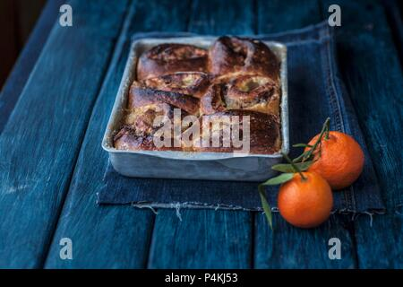 Apple and cinnamon buns in a baking dish next to mandarins - Stock Photo