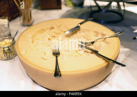 Big wheel of Parmesan cheese on a counter of restaurant self service table with knife and fork - Stock Photo