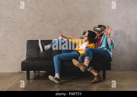 Scared young couple using virtual reality headset on couch - Stock Photo