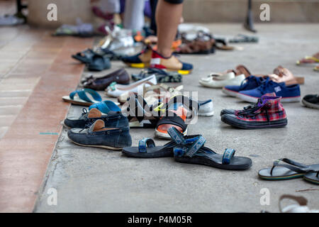 People take off their shoes on the steps in front of the entrance to a famous temple - Stock Photo