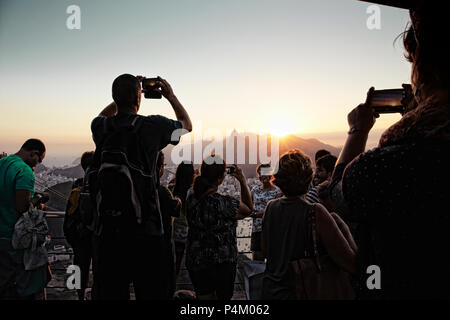 People take photos from Morro da Urca on the Sugarloaf cable car line - Stock Photo