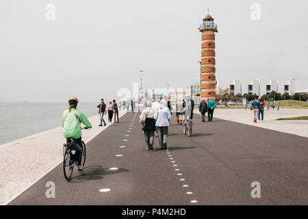 Lisbon, June 18, 2018: People stroll along the promenade in the Belem area. Some people ride bicycles. Ordinary city life