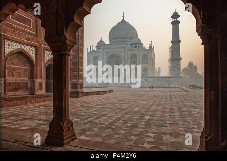 Taj mahal just after sunrise. It can barely be seen due to the high air polution in the Agra area - Stock Photo