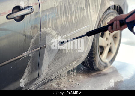 Cleaning Car Using High Pressure Water. Man washing his car under high pressure water in service - Stock Photo