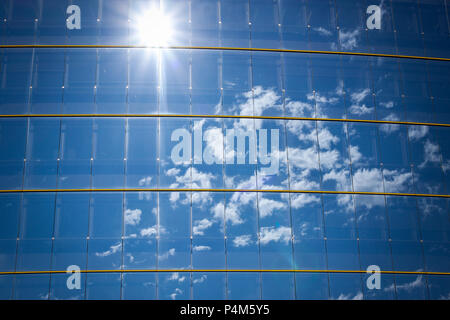 modern office building with glass pattern with sun and clouds reflected - Stock Photo