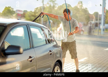 Cleaning the car, car care concept - man car washing by high pressure water and washing foam - Stock Photo