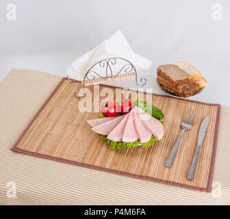 Sliced boiled sausages with tomatoes on lettuce leaves are laid on a plate. Can be used in advertising and creating websites. - Stock Photo