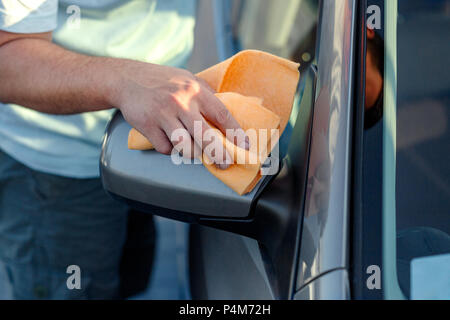 Giving the car a good polish - close up of cleaning car with microfiber cloth, car detailing - Stock Photo