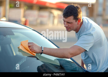 Cleaning like a professional-smiling young man cleaning his car with a microfiber cloth outdoors - Stock Photo