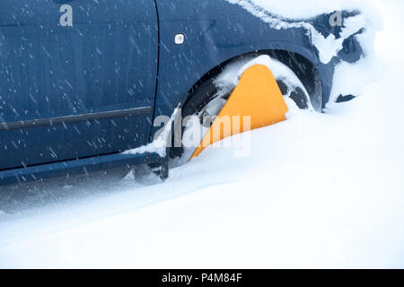 Yellow wheel clamp on a car caught in a snow drift - Stock Photo
