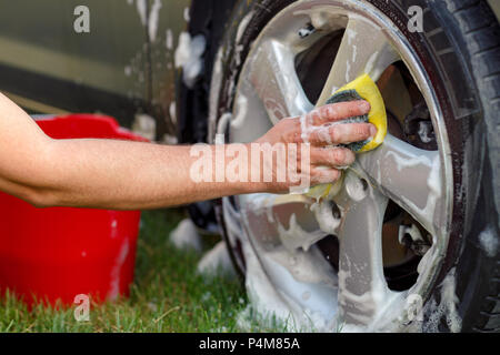 Men's hands are cleaning wheels with a sponge and foam close up - Stock Photo