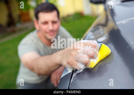 Close up men's hands are cleaning car with yellow sponge and foam - Stock Photo