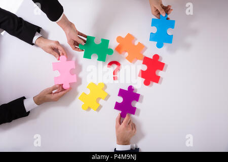 Group Of Businesspeople Holding Jigsaw Puzzle With Question Mark On White Background - Stock Photo