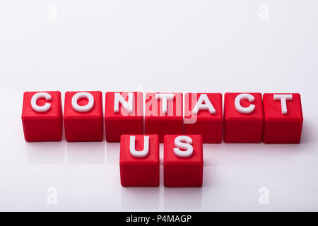 Elevated View Of Red Cubes With Contact Us Text On White Background - Stock Photo