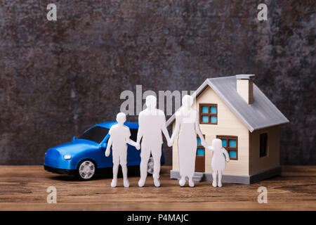 Human Figures Standing In Front Of House And Blue Car On Wooden Plank - Stock Photo