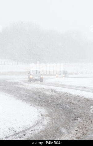 Cars driving along a road in a snow storm in Consett, County Durham, UK, - Stock Photo